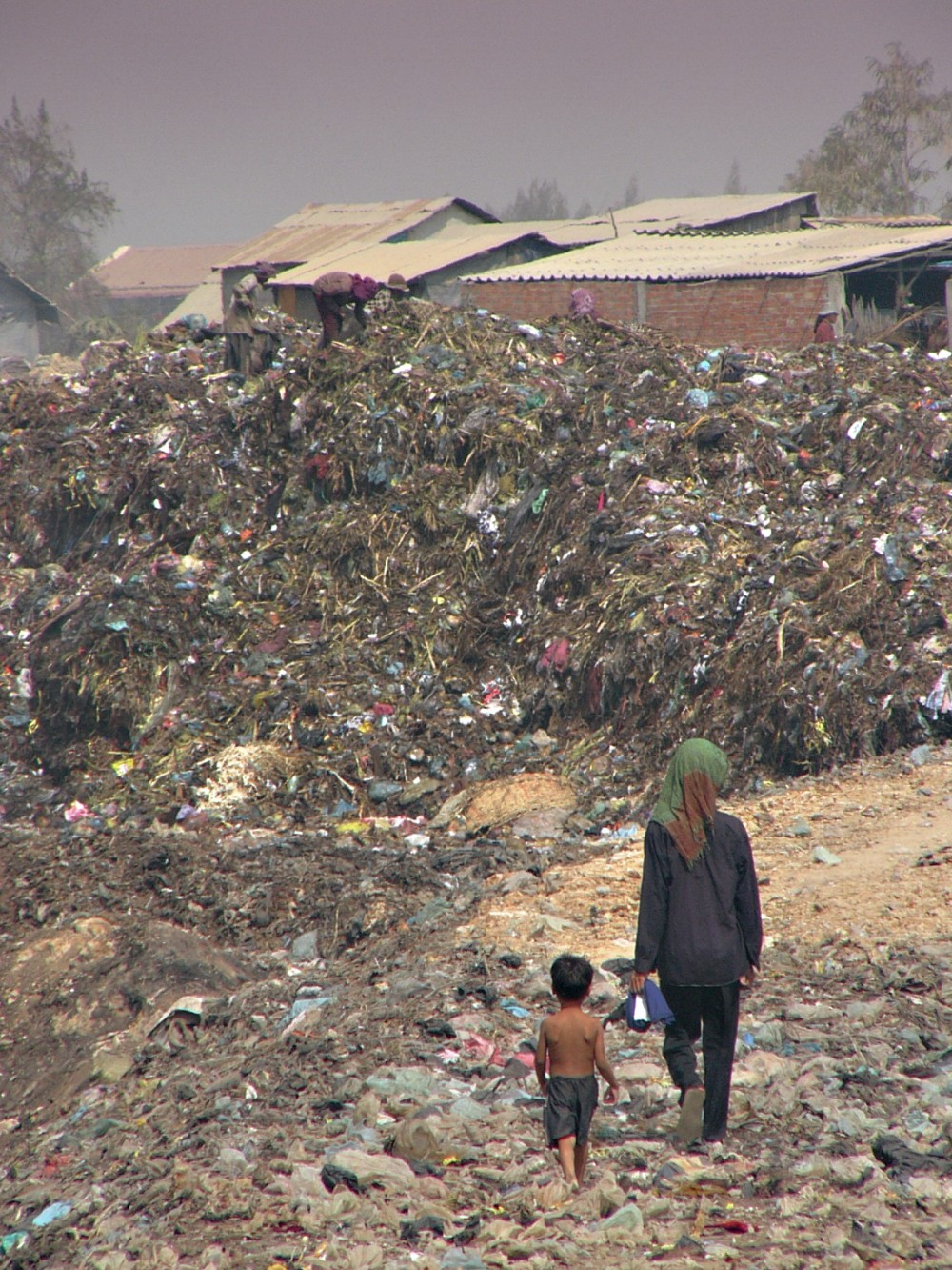 Mother and son walk in trash dump Phnom Penh
