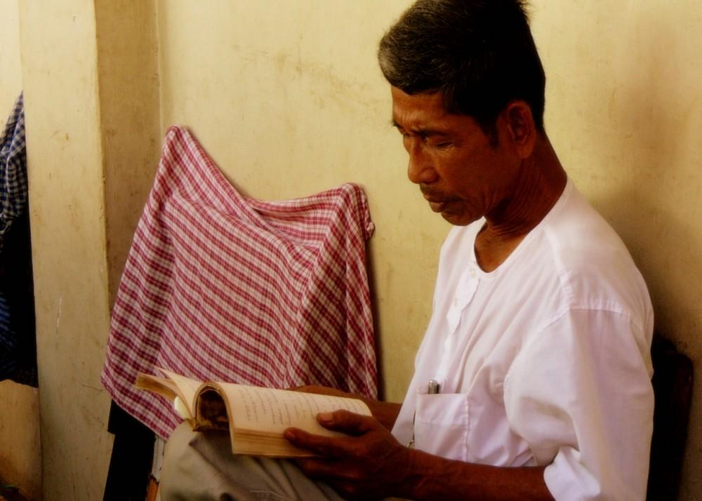 Khmer man reading Buddhist scriptures