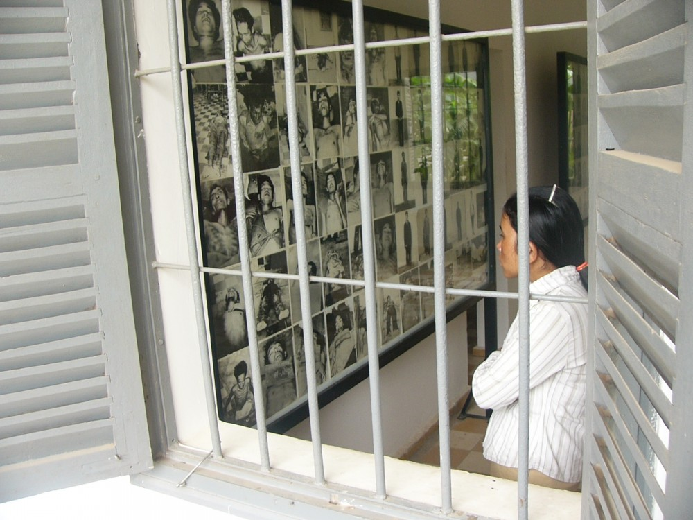 Woman looks at victims of the Khmer Rogue at Tuol Sleng