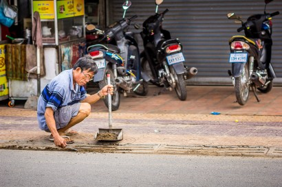 Man Cleans Driveway in Cambodia
